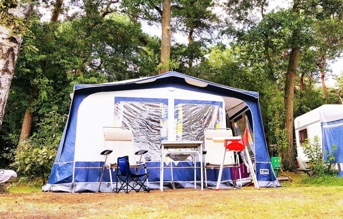Voortent in bos met kinderstoel tijdens kamperen