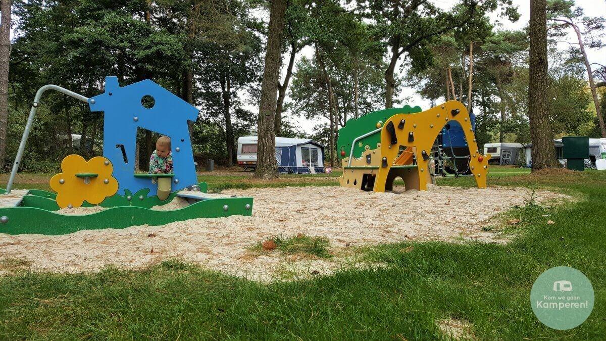 Kind speelt in speeltuintje op camping veld