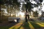 Caravan op rustige camping bij opkomende zon